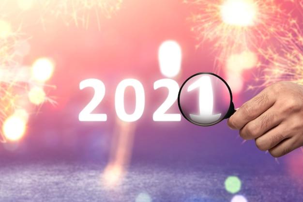 돋보기로 2021을 보여주는 손. 2021 년 새해 복 많이 받으세요