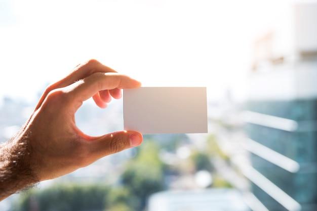 Рука показывает пустую визитную карточку