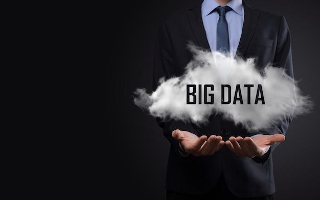 어두운 배경에 빅 데이터라는 단어가 있는 구름을 보여주는 손.