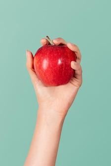 新鮮な赤い赤面リンゴを示す手