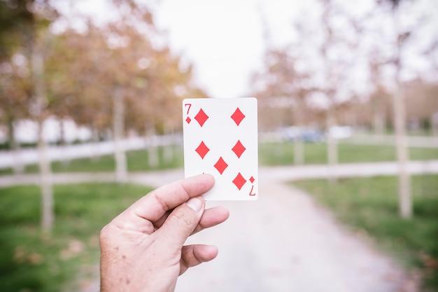 Рука показывает игральную карту на улице