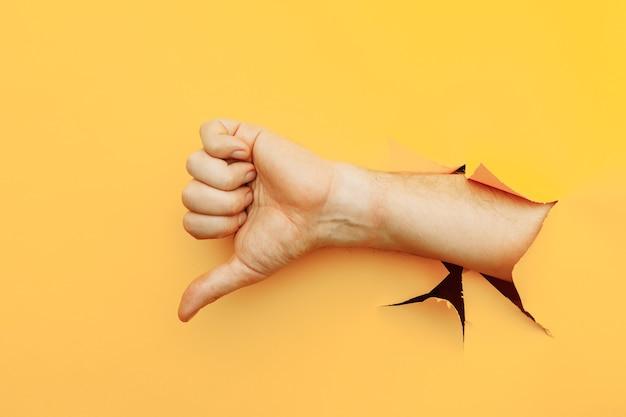 黄色い紙の背景の破れた穴を通して親指を下に示す手嫌いと不承認のジェスチャー