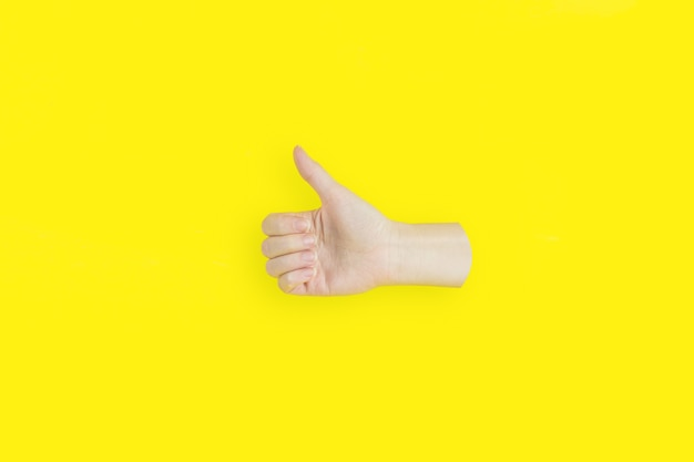 黄色の背景に親指を立てるジェスチャーを示す手。