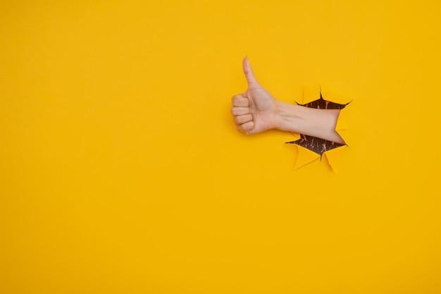 黄色い紙の壁の破れた穴から親指を立てるサインを示す手。よくやった、良い仕事のコンセプト
