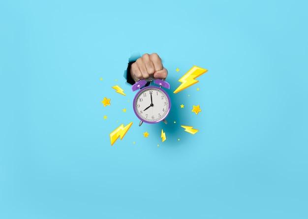 Рука показывает будильник часовая продажа на синем фоне. крайний срок, время для продвижения концепции продажи.