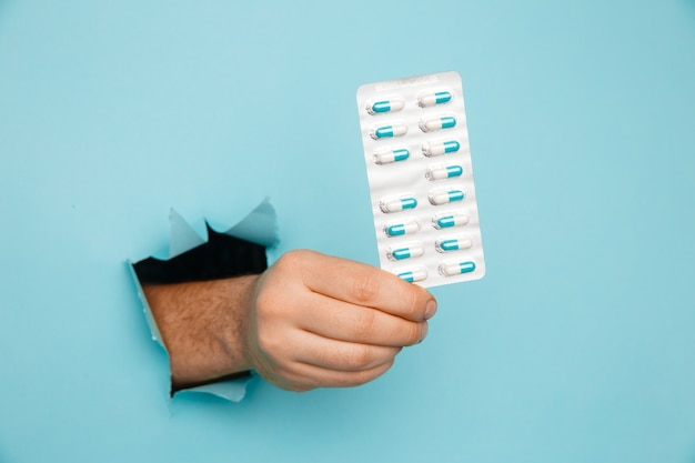 Hand showing a blister of pills out of a hole torn in blue paper wall. health care, pharmaceutics and medicine advertisement