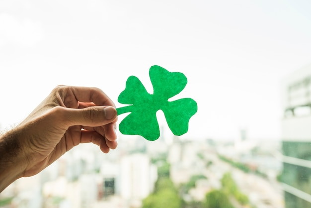 Hand showing green paper shamrock and view of cityscape