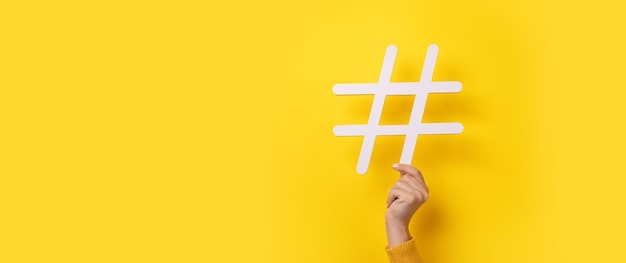 노란색 배경, 비즈니스 개념, 파노라마 모형 위에 hashtag를 보여주는 손