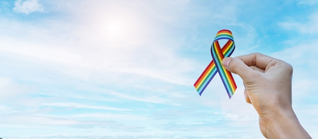 Hand showing lgbtq rainbow ribbon against sky background in the morning.
