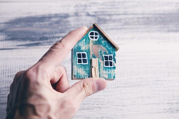 小さな古い家のモデルを示す手