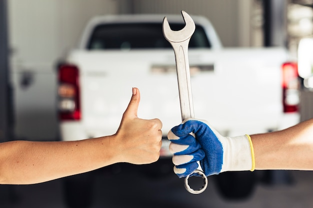 Hand showing ok sign and holding wrench