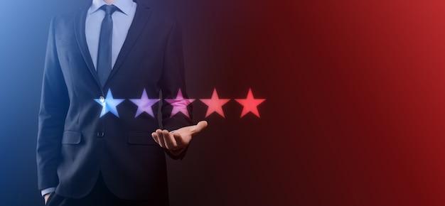 Рука, показывающая на пятизвездочном отличном рейтинге. указание пятизвездочного символа для повышения рейтинга компании