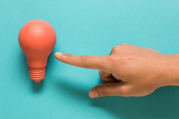 Hand showing on pink lamp on colored surface