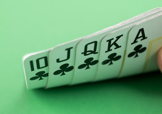 Hand showing royal flush over green background.