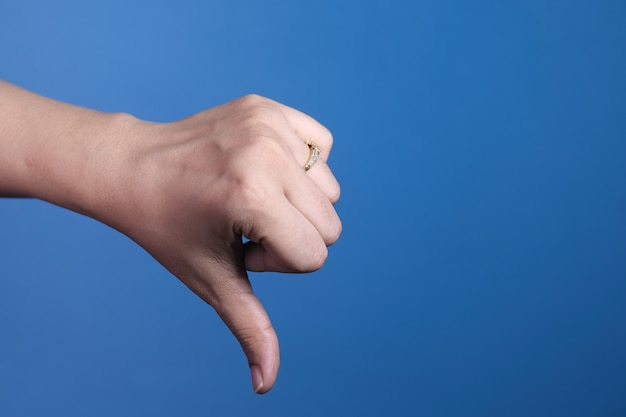 Hand showing thumb down sign on blue background.