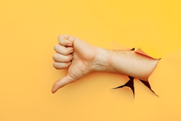 Hand showing a thumb down through ripped hole in yellow paper background dislike and disapproval gesture