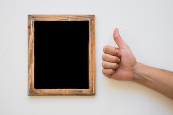 Hand showing thumb up sign near the blackboard