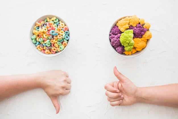 Hand showing thumbsup and thumbs down gesture in front of cereal and cauliflower bowl
