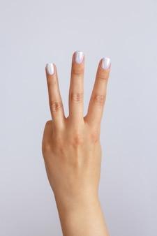 手は3番目を示しています。カウントダウンジェスチャーまたはサイン。手話