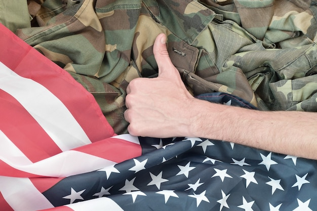 Hand shows thumbs up on american flag and military uniform. concept of good military service in united stated