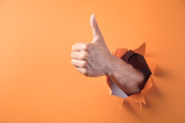 手はオレンジ色の背景に親指を立てるサインを示しています