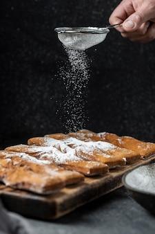 デザートに粉砂糖を手でふるいにかける