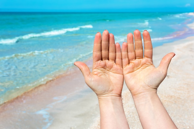 Hand sign over blue sea and sky, summer travel