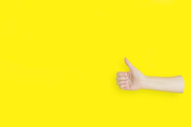 黄色の背景にコピースペースで親指を立てる手サイン。
