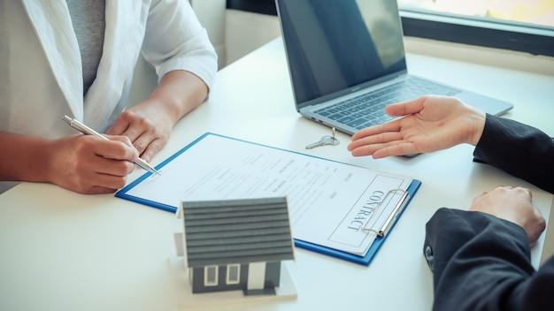 Подписание договора вручную после того, как агент по недвижимости объясняет покупателю страхование жилья подрядчика