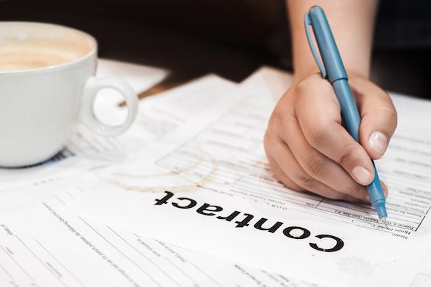 汚れた契約書に手で署名する