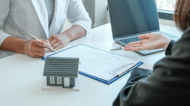 Подписание контракта вручную после того, как агент по недвижимости объяснит покупателю коммерческий контракт, аренду, покупку, ипотеку, ссуду или страхование жилья.