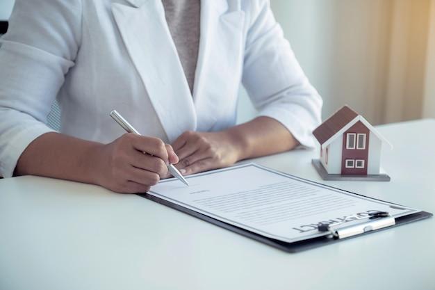 Подписание контракта вручную после того, как агент по недвижимости разъясняет покупателю коммерческий контракт.