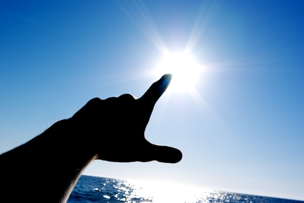 Hand silhouette pointing to the sun