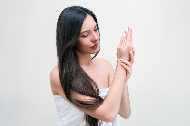 ハンドスキンとボディケア。タオルで美しい若い女性が彼女の肌に触れる