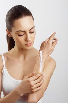 ハンドスキンケア。クリームを適用する女性の手のクローズアップ