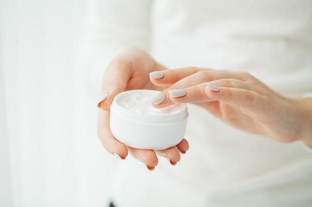 ハンドスキンケア。クリームチューブを保持している女性の手のクローズアップ、柔らかい絹のような健康な肌に化粧品のハンドクリームを適用する天然マニキュアの爪を持つ美しい女性の手。
