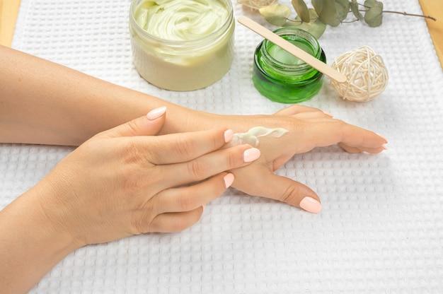 ハンドスキンケア。クローズアップ大人の成熟した女性の手と自然なマニキュアの爪。彼女の柔らかい絹のような健康な肌に触れる女性の手のクローズアップ。美容と健康、大人の成熟した肌のコンセプト