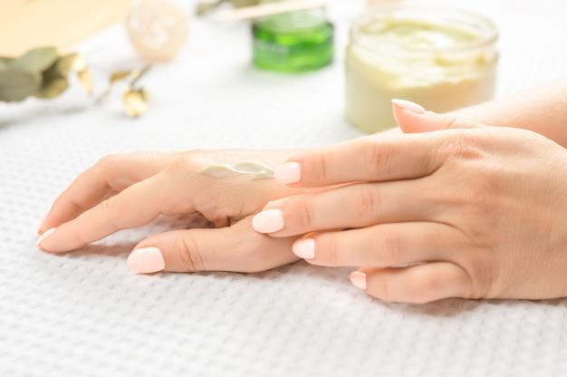 ハンドスキンケア。自然なマニキュアの爪を持つ美しい女性の手のクローズアップ。彼女の柔らかな絹のような健康な肌に保湿クリームを適用する女性の手のクローズアップ。美容と健康。セレクティブフォーカス