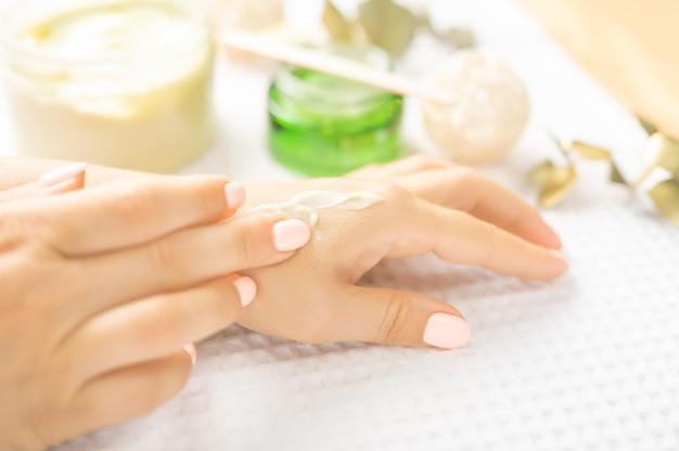 ハンドスキンケア。自然なマニキュアの爪を持つ美しい女性の手のクローズアップ。彼女の柔らかい絹のような健康な肌に触れる女性の手のクローズアップ。美容と健康、ボディケアのコンセプト。セレクティブフォーカス