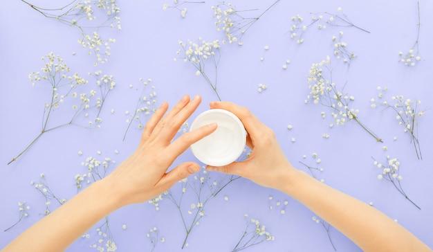 Крем для ухода за кожей рук в женских руках с применением органической натуральной косметики с цветами