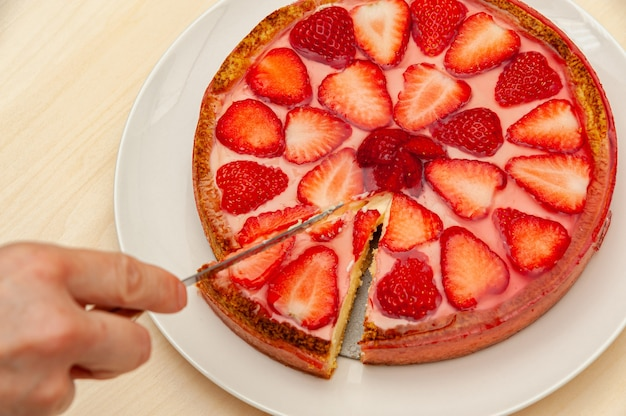Hand slicing delicious homemade strawberry tart isolated on wooden background
