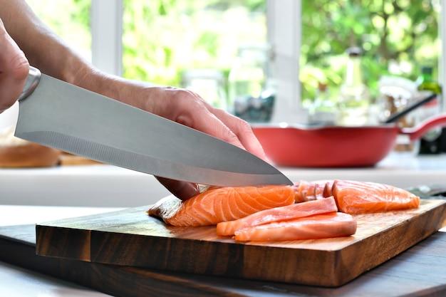 Ручная нарезка стейков из свежего сырого филе лосося на разделочной доске на кухне