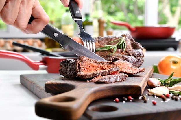 부엌에 있는 나무 도마에 향신료와 함께 구운 쇠고기 스테이크를 손으로 썰어라