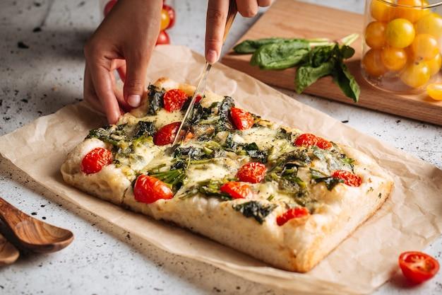 Рука нарезка итальянского хлеба фокачча со шпинатом