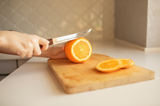 Hand slicing orange on wooden board