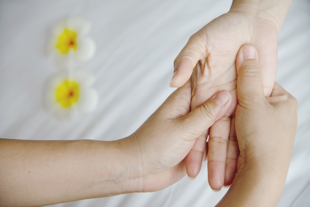 Hand spa massage over clean white bed  - people relax with hand massage service