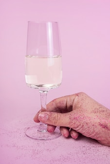 Hand in spangles holding champagne glass on table