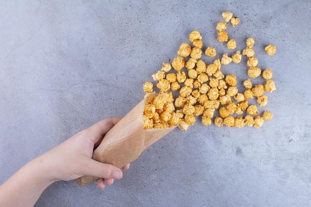 A hand spilling out a pack of caramel coated popcorn on marble surface