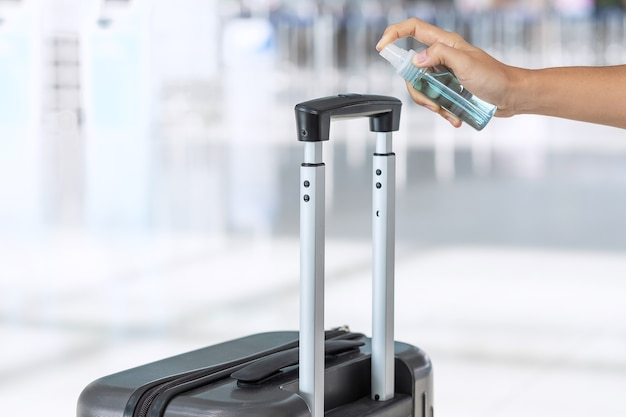 Hand spraying alcohol sanitizer on handle luggage bag in the airport