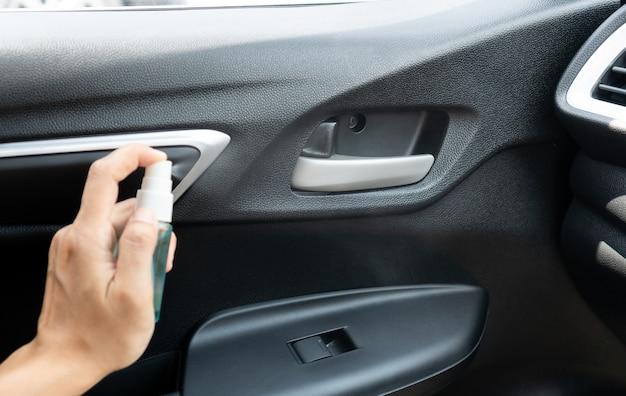 消毒のために車のオープナーにアルコールを手でスプレーします。コロナウイルス、covid-19中の表面の洗浄